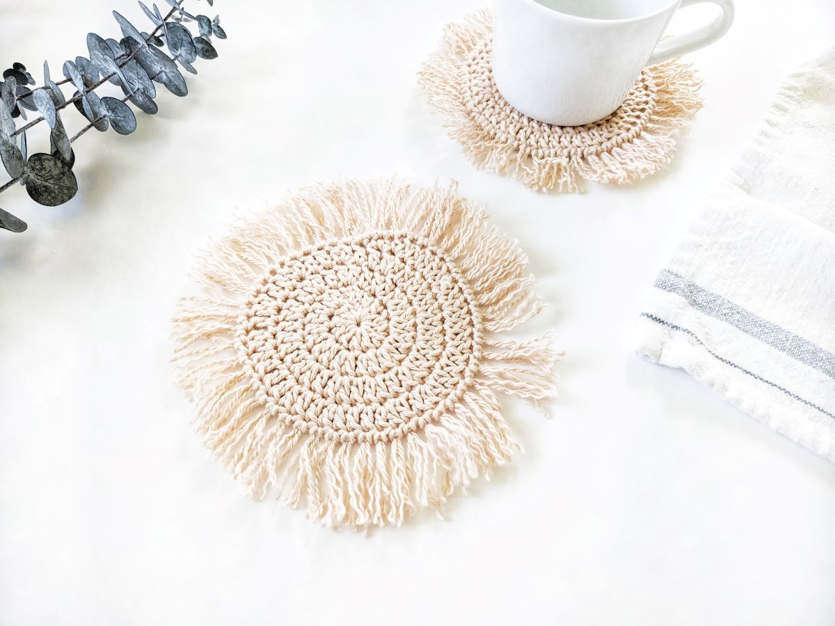 cotton boho crochet coaster with fringe and white tea cup and tea towel