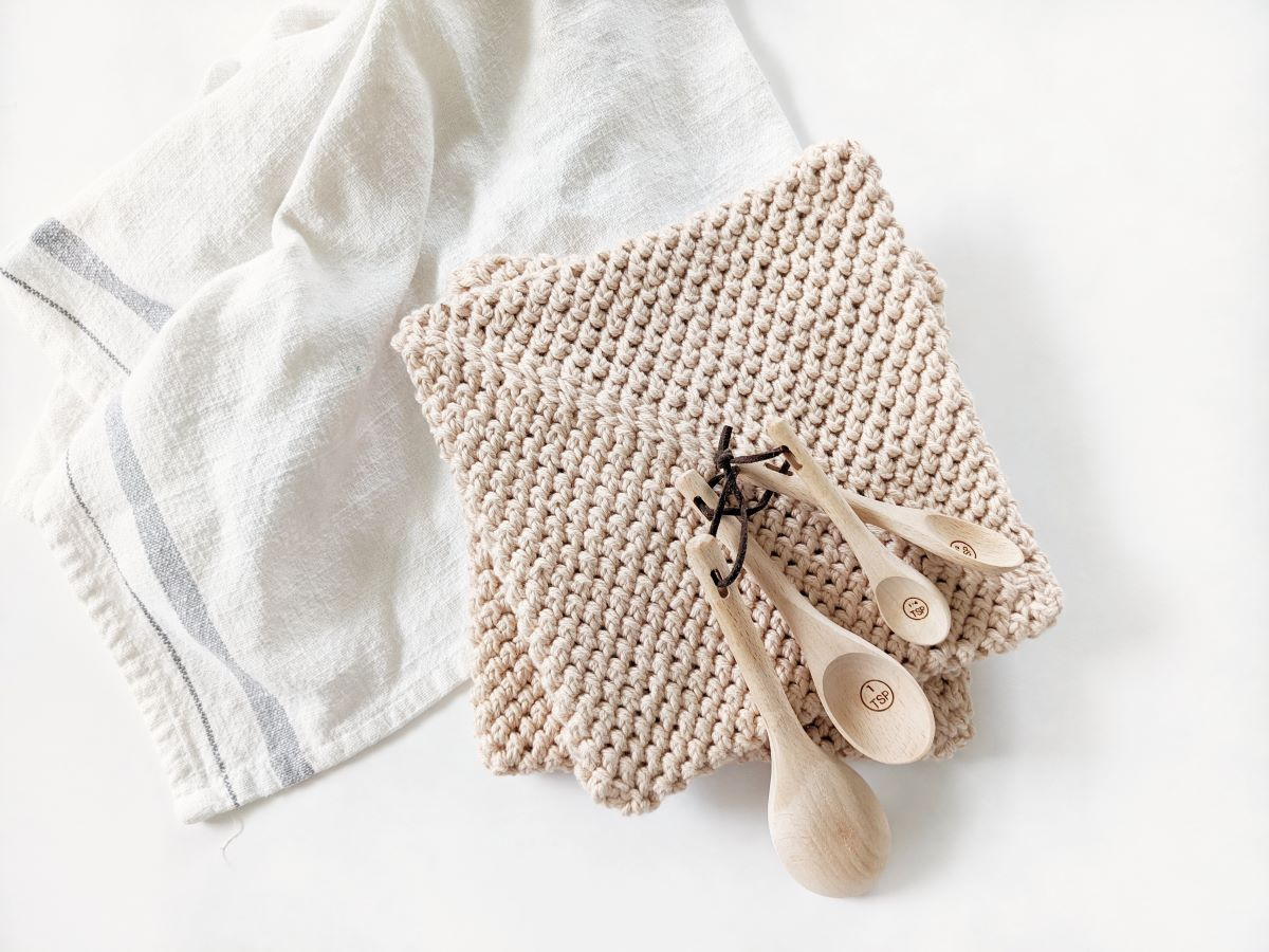 2 modern double thick cotton crochet potholders with wooden measuring teaspoons on top and a tea towel