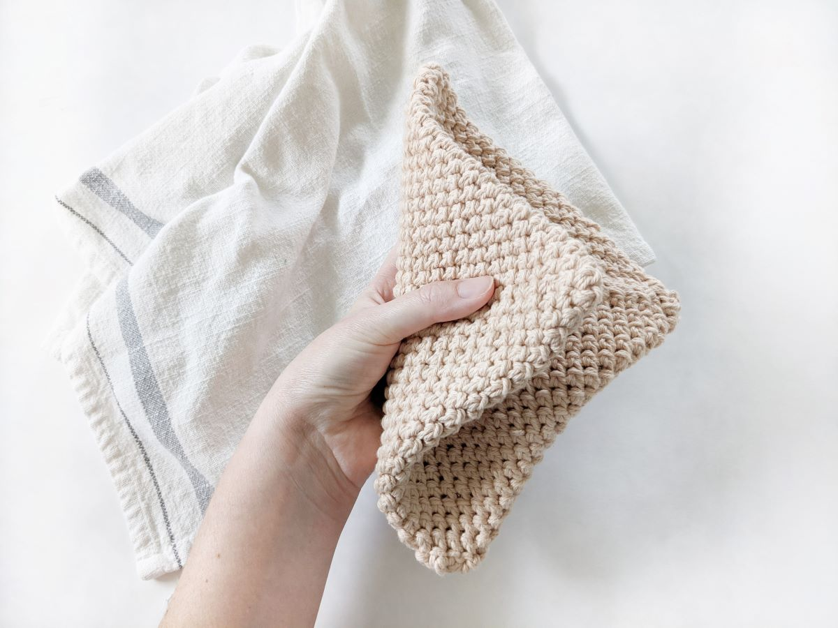 a double thick crochet cotton potholder folded with a tea towel in the background