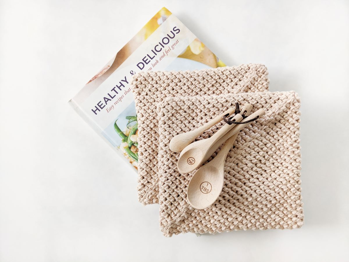a stack of double thick crochet potholders with measuring spoons and a cookbook