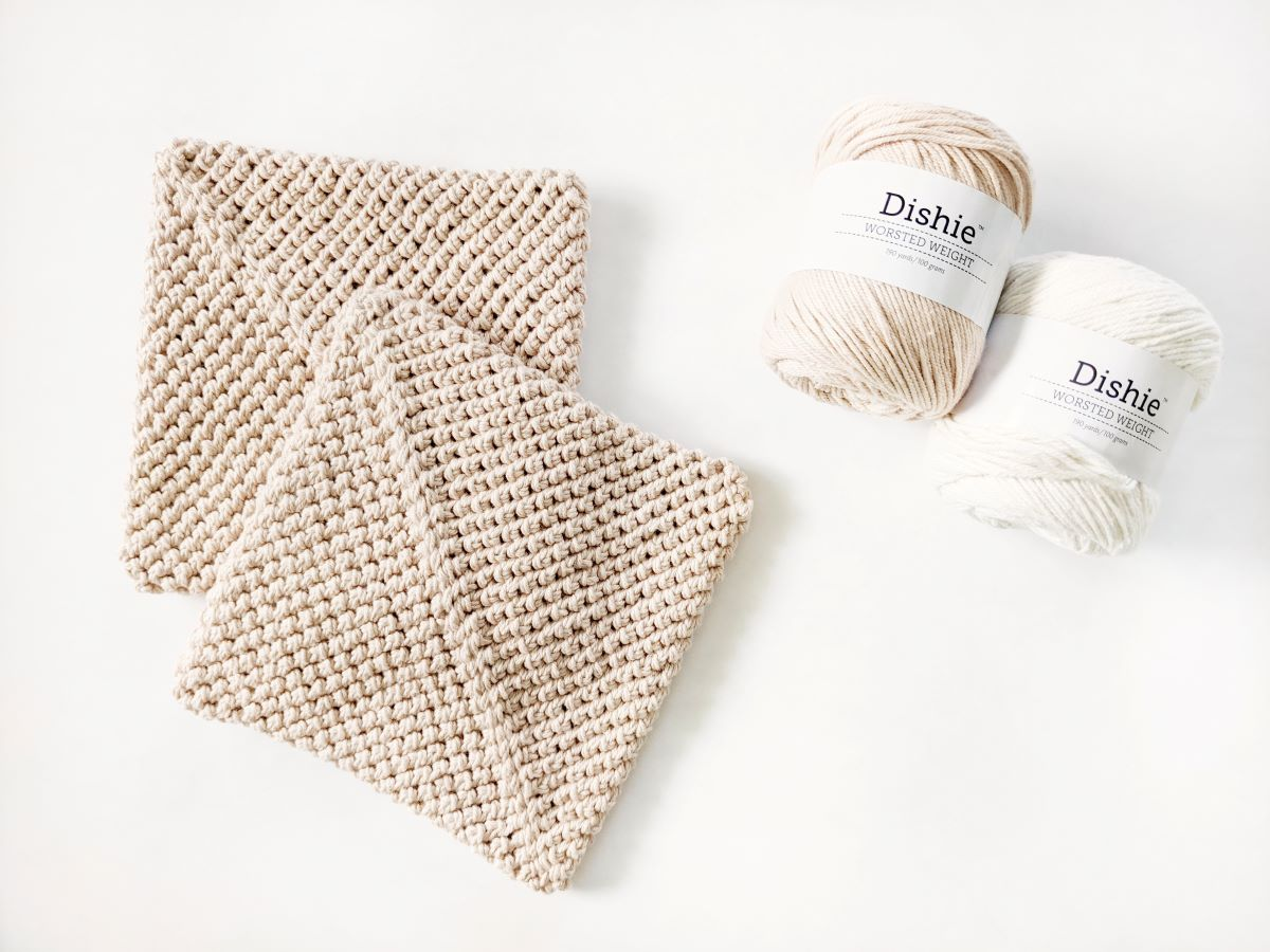 two crochet potholders with WeCrochet Dishie yarn balls in the color linen and swan