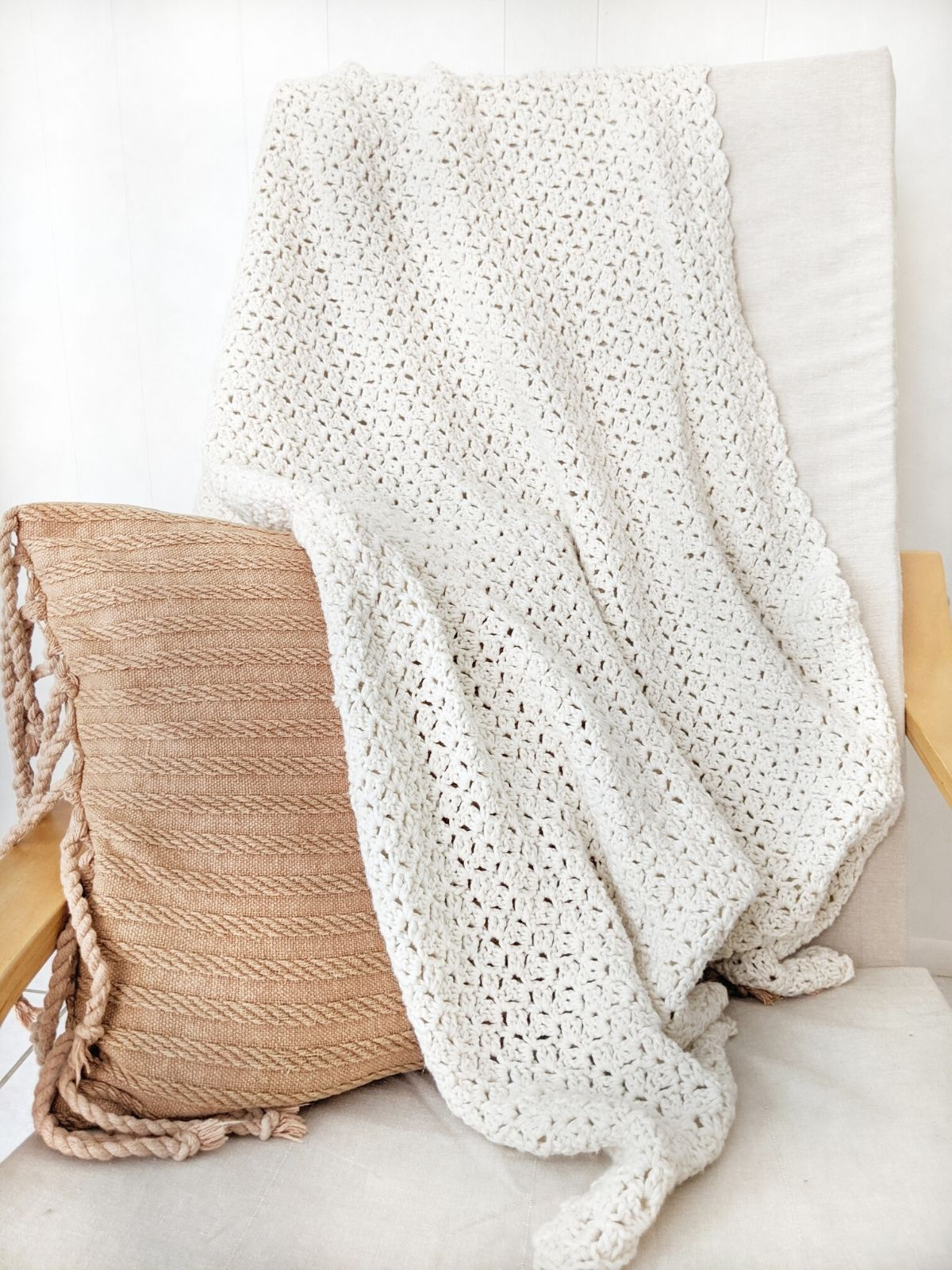 cotton crochet blanket on a Ikea chair with a boho fringe orange pillow