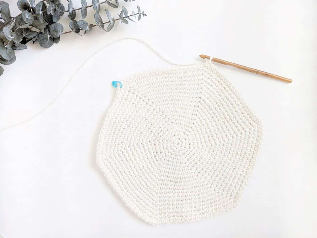 a work in progress image of a single crochet placemat with a wooden crochet hook and stitch marker