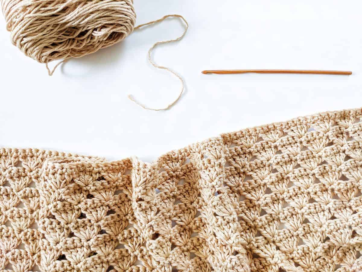a progress photo showing how to make the shell stitch with a wooden crochet hook