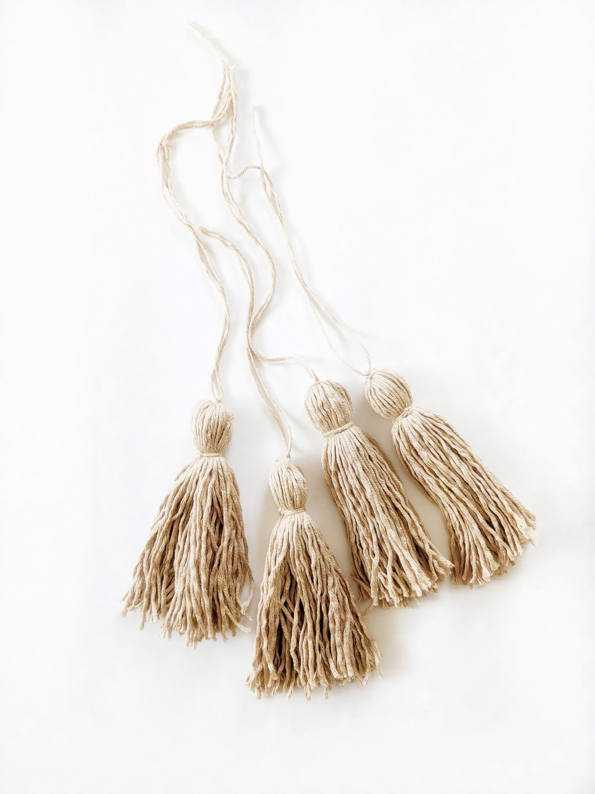 4 handmade tassels on a white surface using Lion Brand Coboo yarn