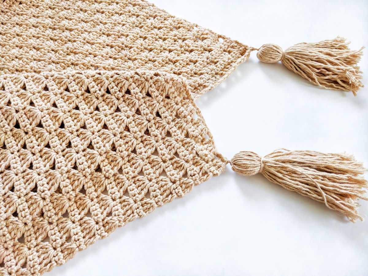 a crochet shell stitch baby blanket with 2 bamboo cotton yarn tassels on a white surface