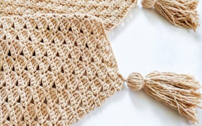 a shell stitch baby blanket with two tassels on a clean white background