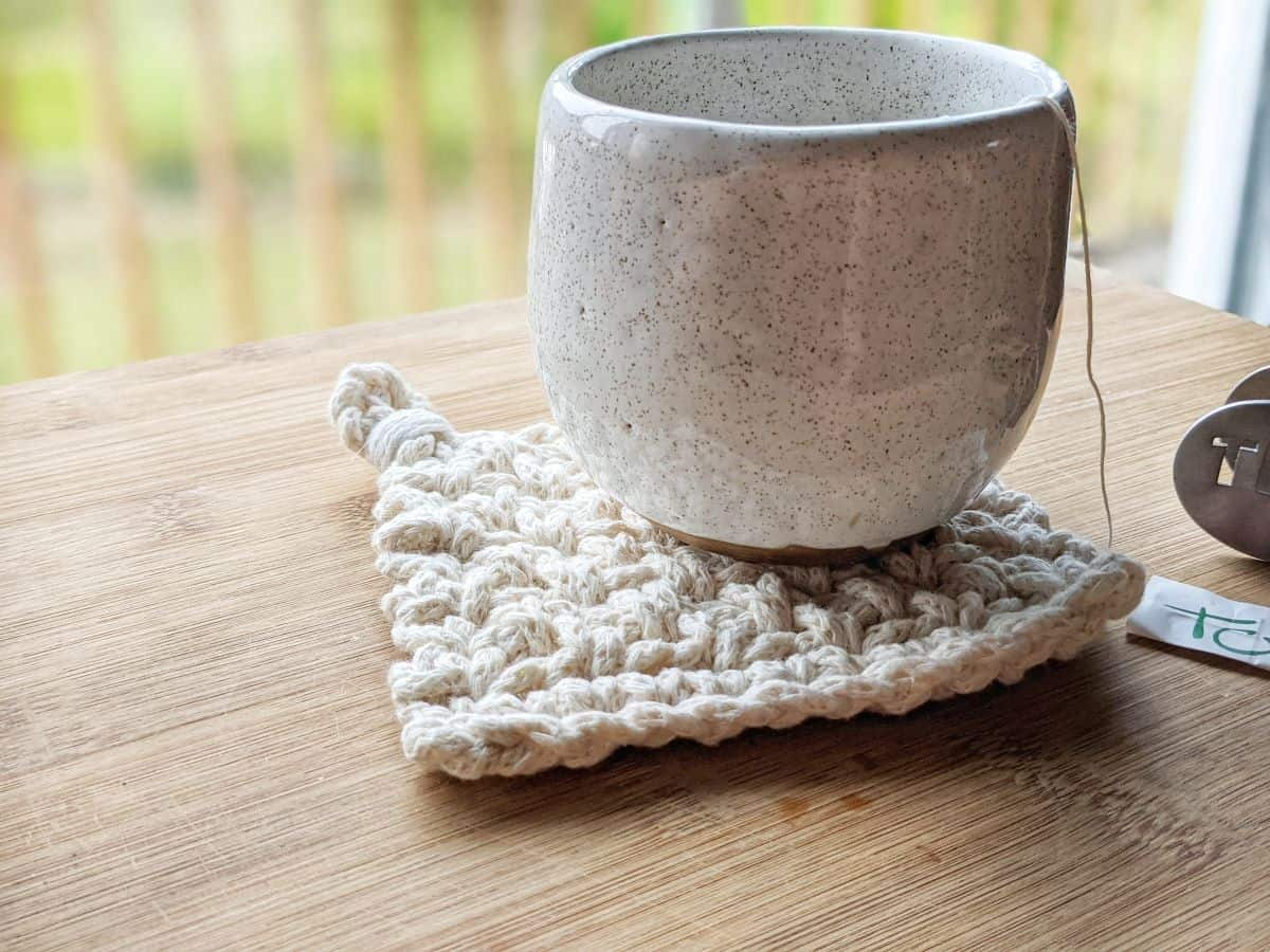 a modern chunky white crochet coaster with a ceramic mug on top on a wooden table