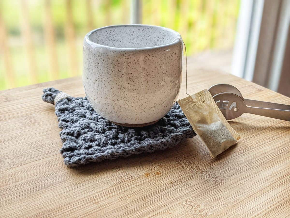 a chunky cotton blue crochet coasters with a white cup on it