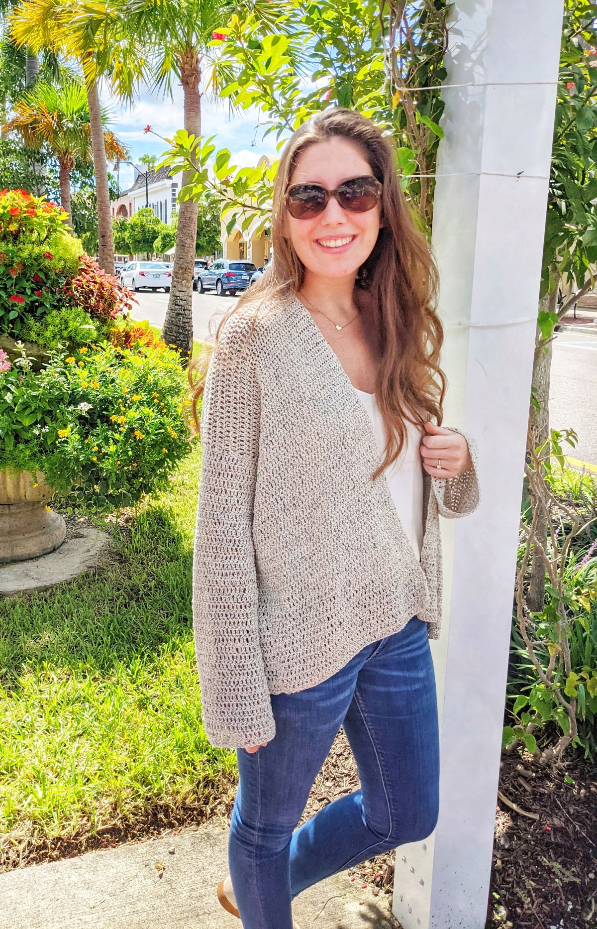 model is wearing a long crochet cardigan with jeans and a white t-shirt behind a grassy surrounding