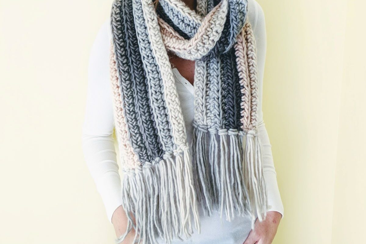 a person wearing a chunky crochet scarf with a white shirt and a pair of jeans