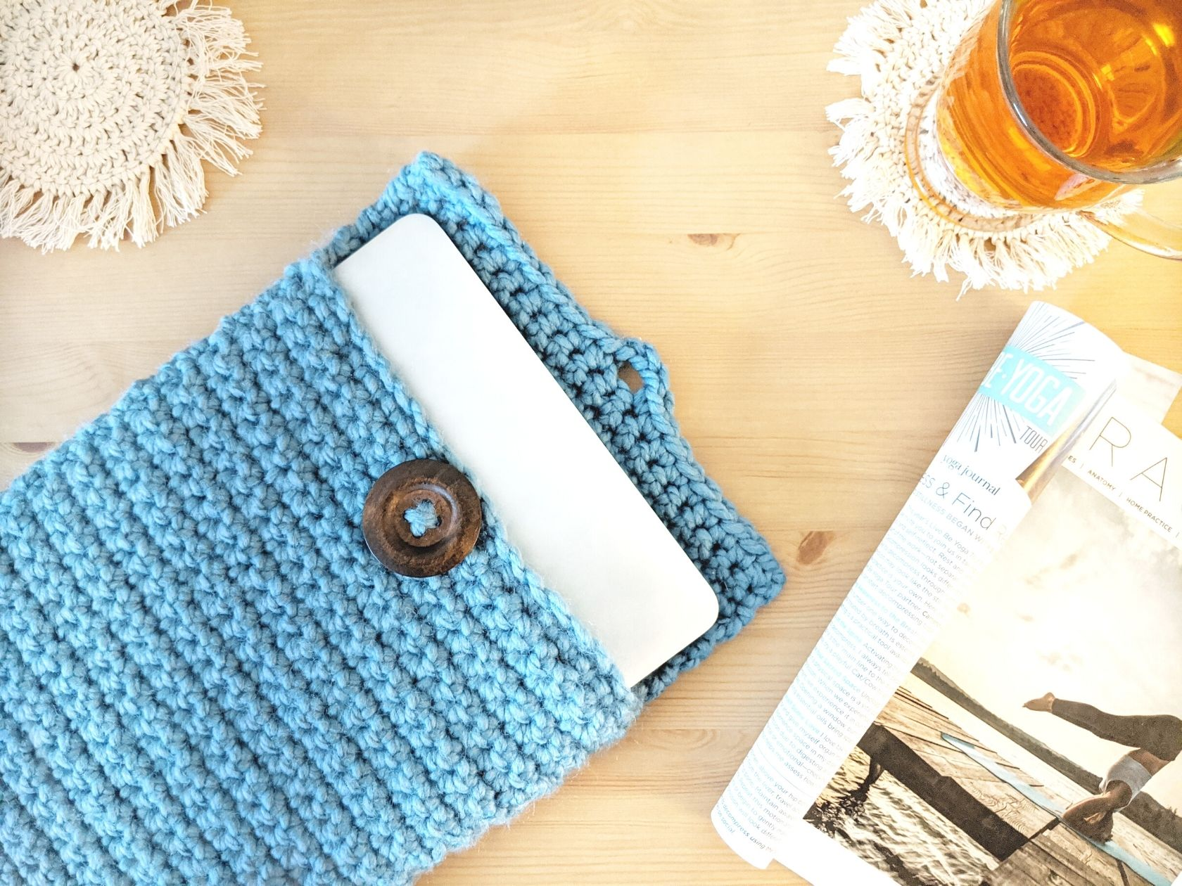 chunky crochet laptop cover on a wooden table with a magazine, coaster, and tea