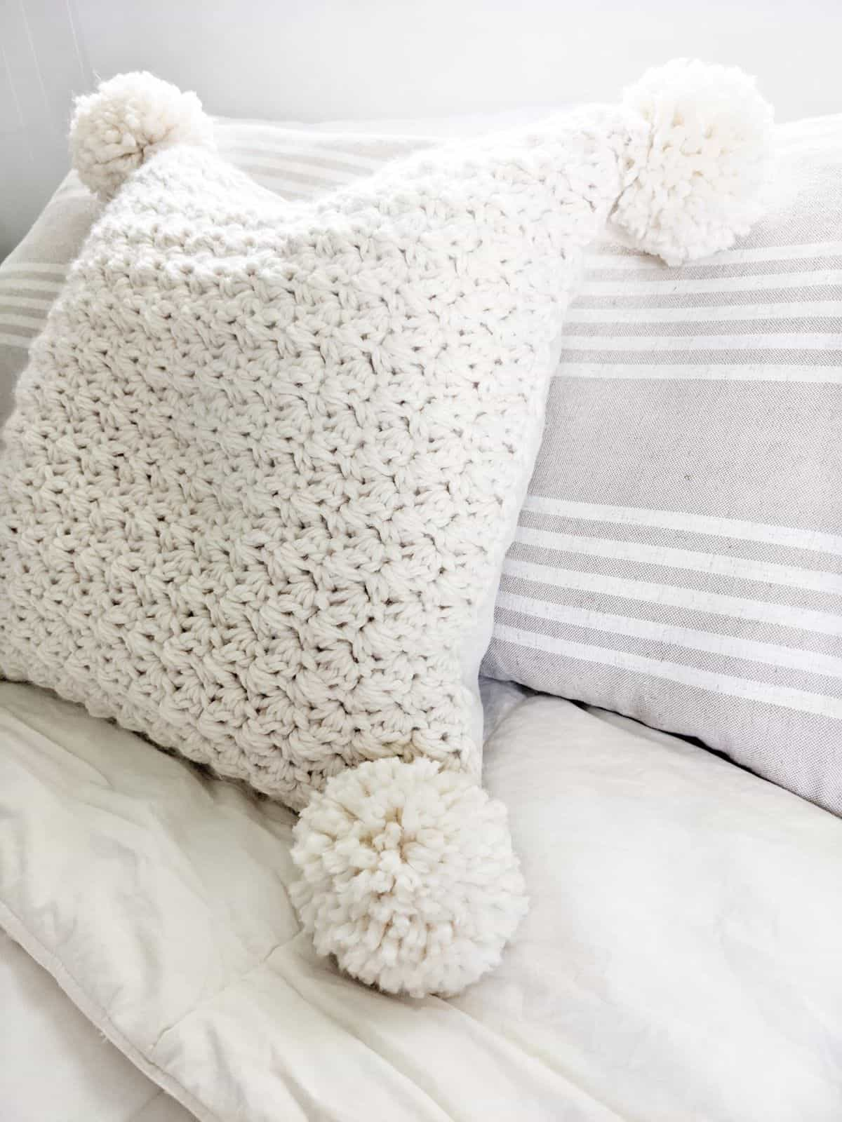 side angle of a bulky crochet pillow made with pom poms in the color natural