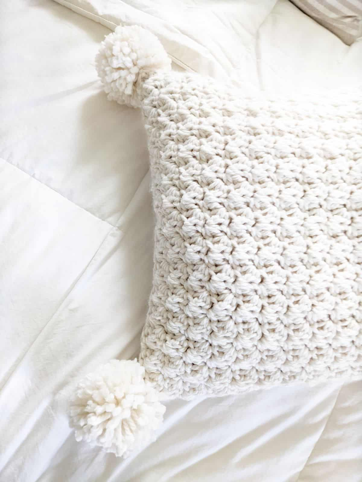 a chunky crochet pillow on a bed with a white cover