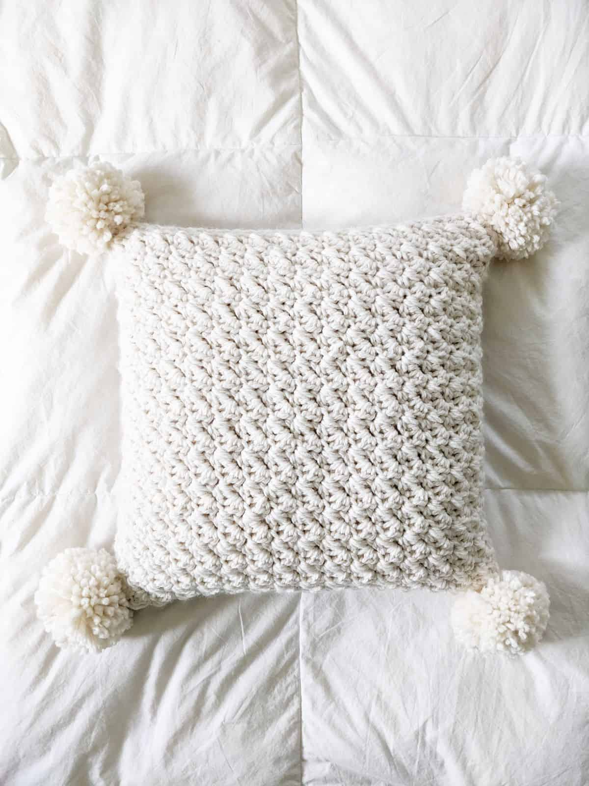 a crochet chunky pillow with 4 pom poms in the color fisherman