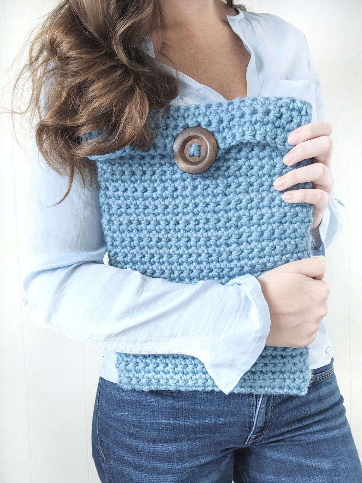 girl holds a crochet laptop case in the color blue with a button