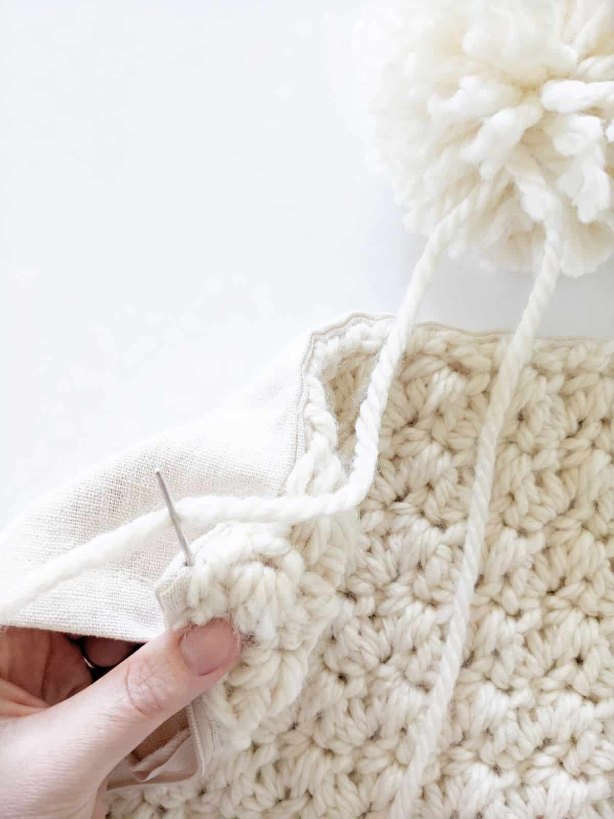 how to attach your pom pom to your crochet pillow cover