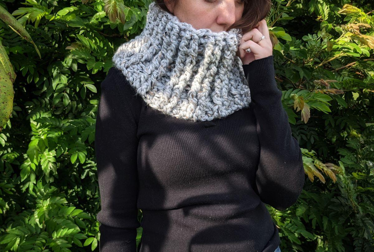 model has a chunky crochet cowl with a long sleeve shirt on