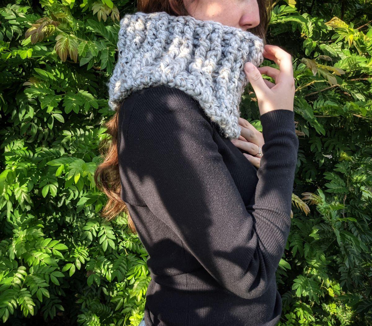 model is wearing a grey crochet cowl
