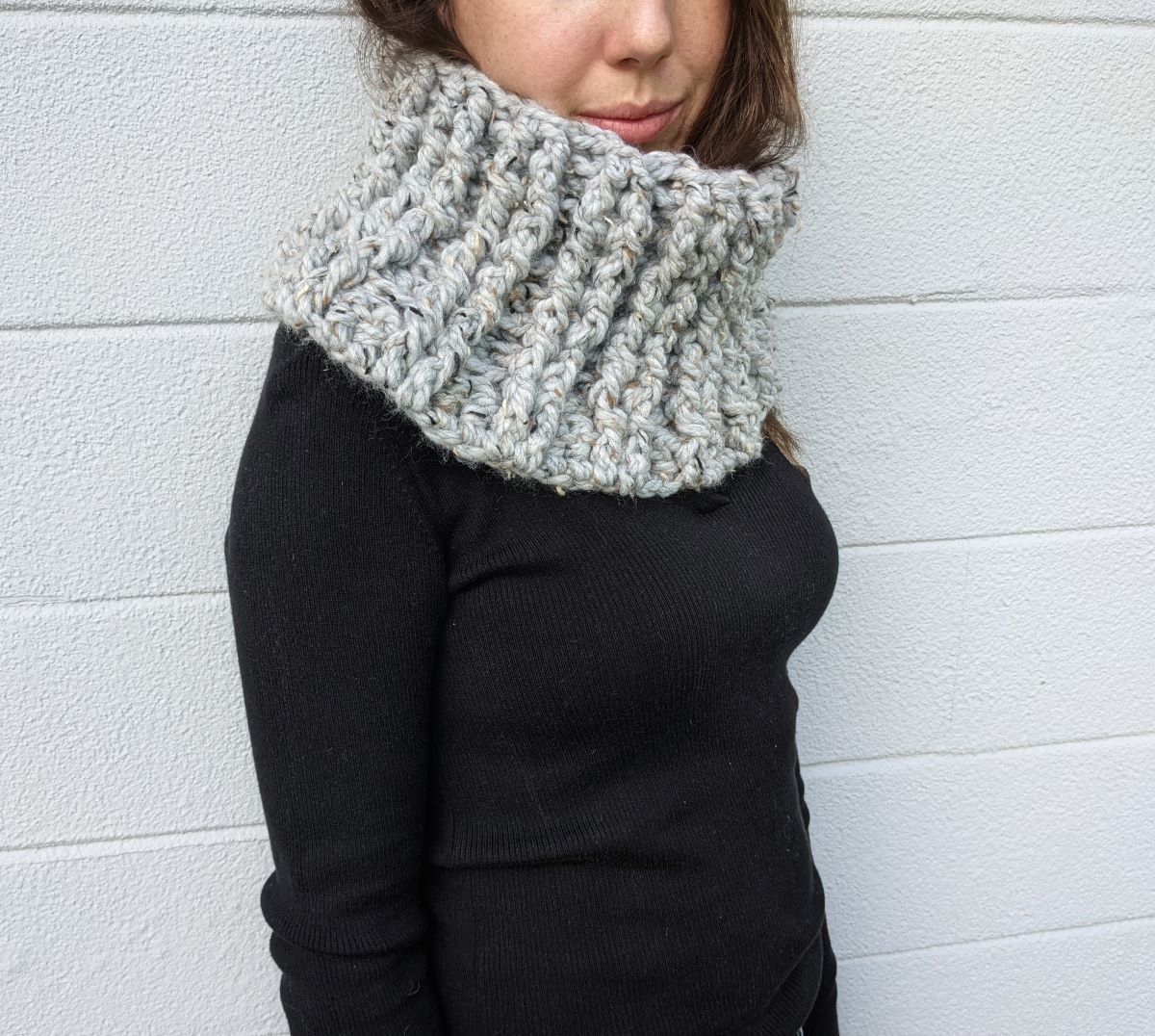 model wearing a chunky crochet cowl with a long sleeve black top