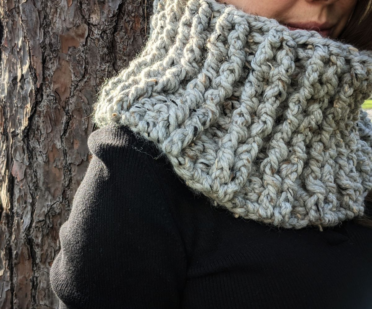 model is wearing a bulky weight crochet cowl in the color grey