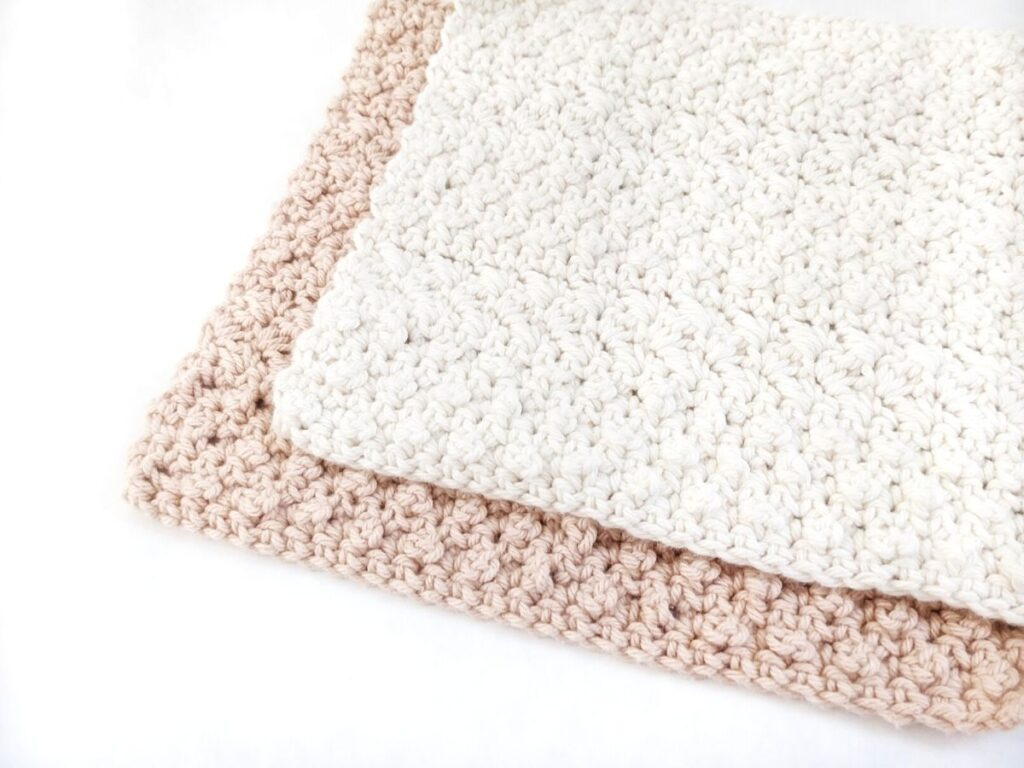 2 crochet dishcloths on a white board