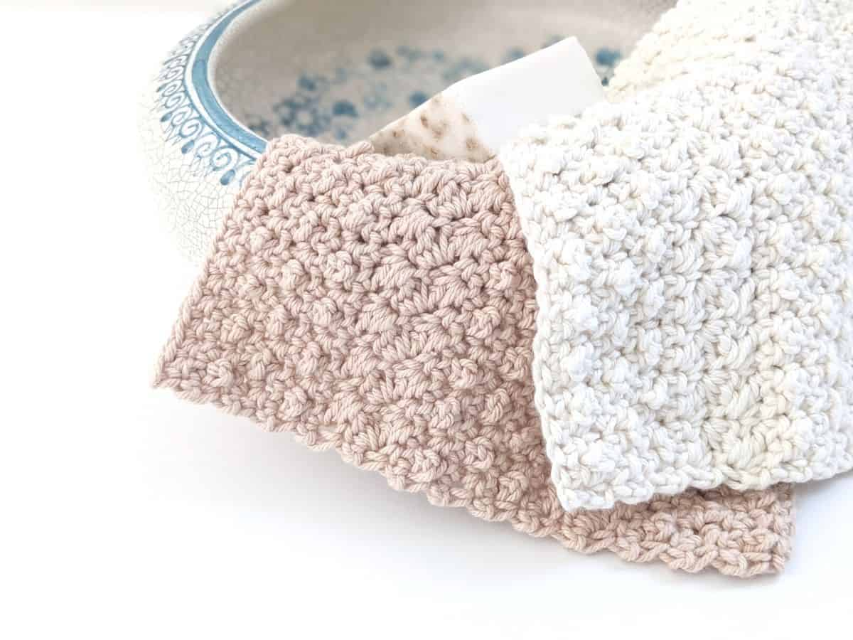2 rustic crochet dishcloths with a bar of soap in a ceramic bowl
