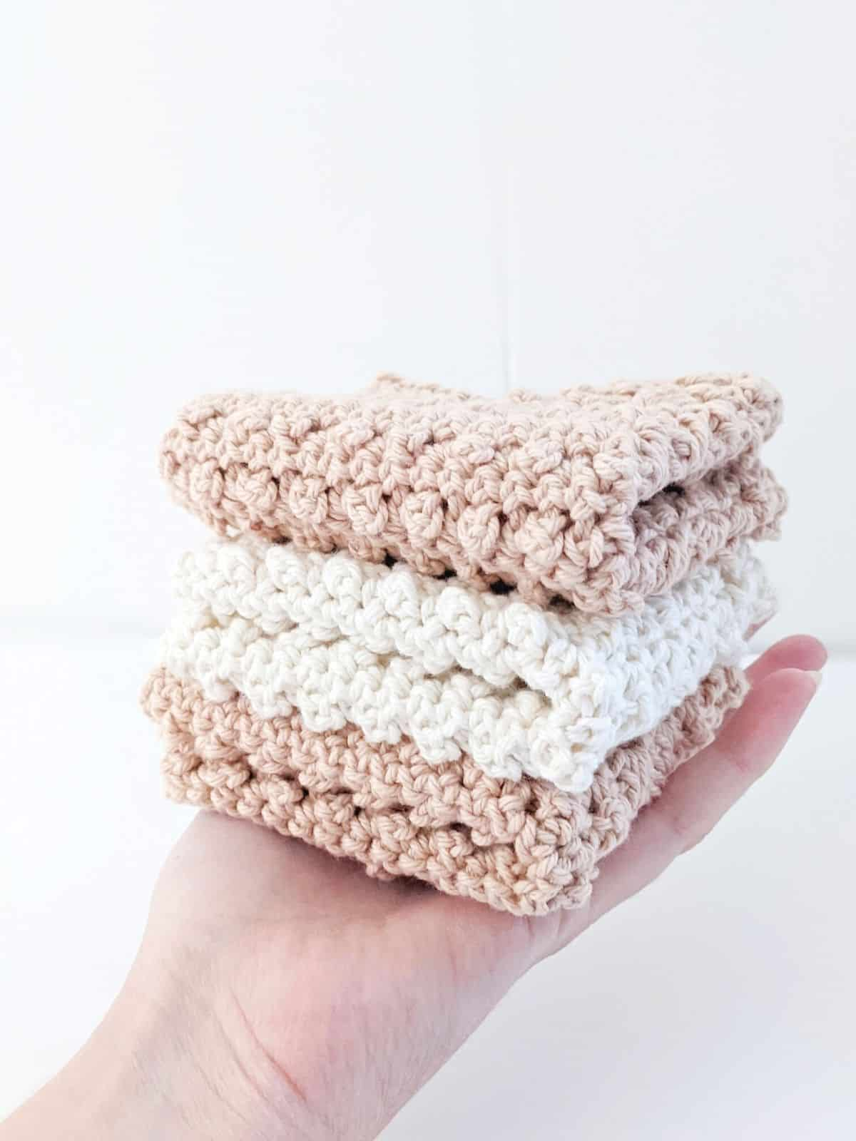 model holding 3 folded crochet dishcloths in the color white and linen