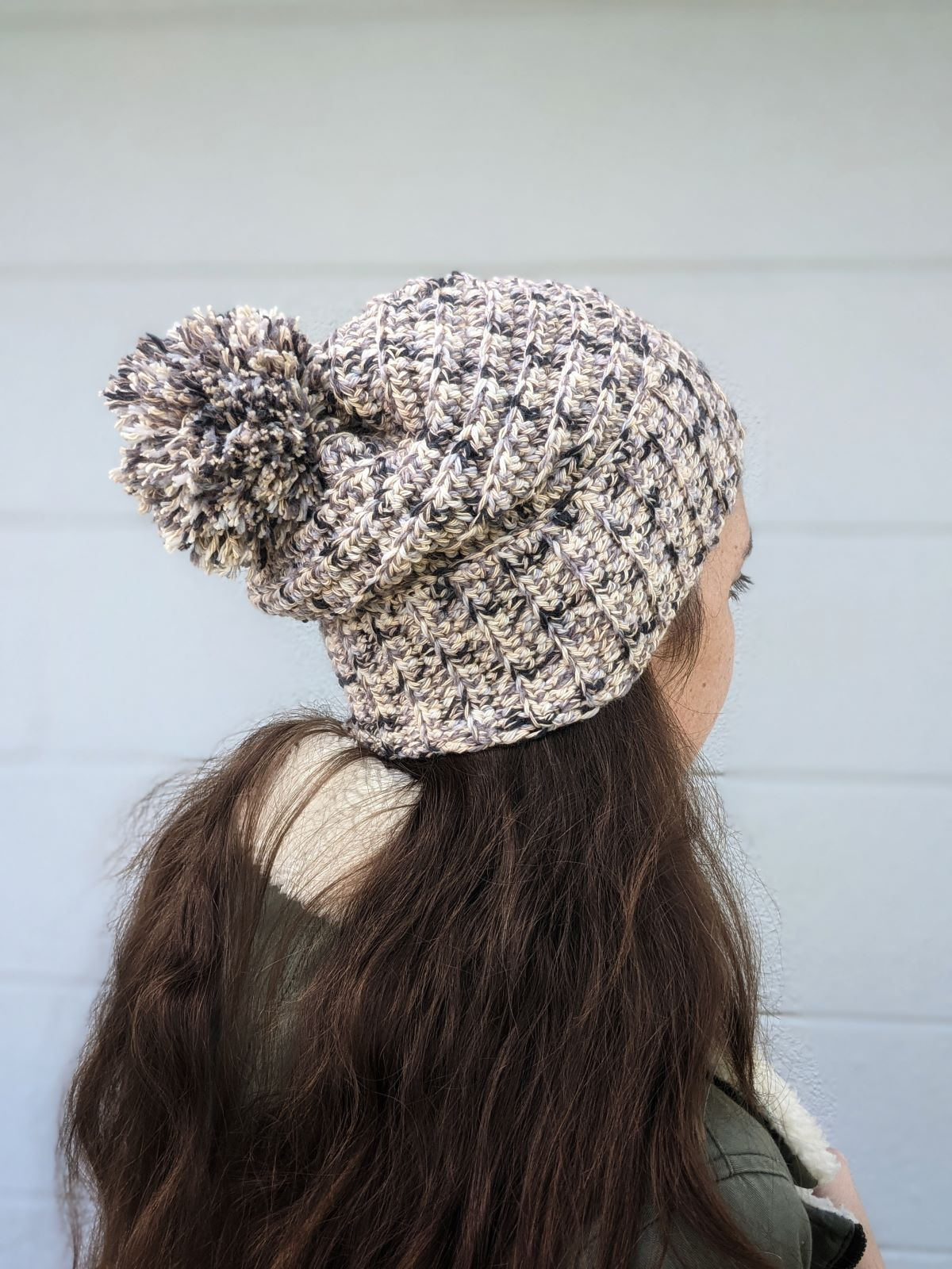 model is wearing a cotton crochet slouchy beanie with a pom-pom